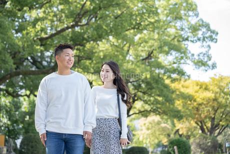 綺麗な緑を背景に仲良く歩く若い男女の写真素材 [FYI03414255]