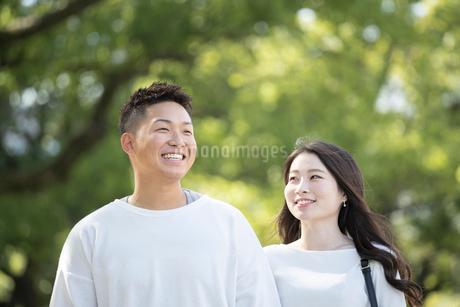 綺麗な緑を背景に仲良く歩く若い男女の写真素材 [FYI03414256]