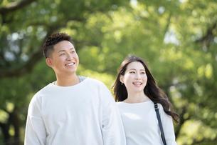綺麗な緑を背景に仲良く歩く若い男女の写真素材 [FYI03414257]