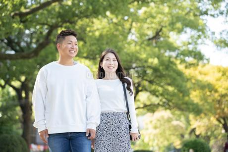 綺麗な緑を背景に仲良く歩く若い男女の写真素材 [FYI03414258]