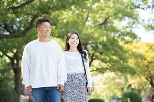 綺麗な緑を背景に仲良く歩く若い男女の写真素材 [FYI03414259]