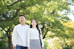 綺麗な緑を背景に仲良く歩く若い男女の写真素材 [FYI03414260]