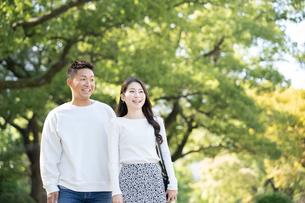 綺麗な緑を背景に仲良く歩く若い男女の写真素材 [FYI03414261]