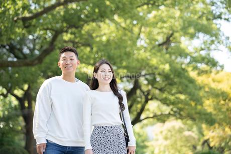 綺麗な緑を背景に仲良く歩く若い男女の写真素材 [FYI03414262]
