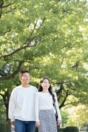 綺麗な緑を背景に仲良く歩く若い男女の写真素材 [FYI03414263]