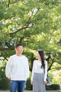 綺麗な緑を背景に仲良く歩く若い男女の写真素材 [FYI03414264]