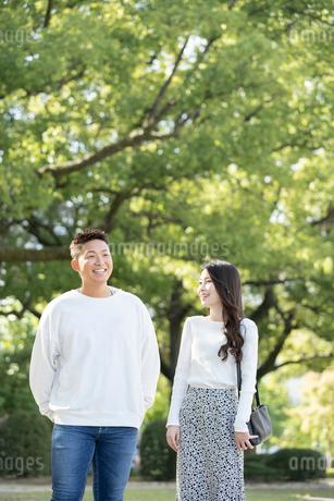 綺麗な緑を背景に仲良く歩く若い男女の写真素材 [FYI03414265]
