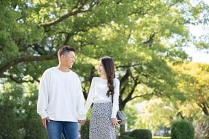 綺麗な緑を背景に仲良く歩く若い男女の写真素材 [FYI03414266]