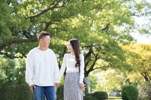 綺麗な緑を背景に仲良く歩く若い男女の写真素材 [FYI03414267]