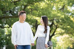 綺麗な緑を背景に仲良く歩く若い男女の写真素材 [FYI03414268]