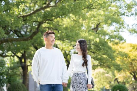 綺麗な緑を背景に仲良く歩く若い男女の写真素材 [FYI03414270]
