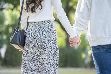 仲良く手を繋ぐ若い男女の後ろ姿の写真素材 [FYI03414272]