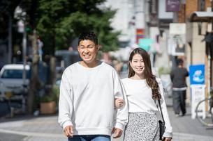 街中で仲良くデートをする若い男女の写真素材 [FYI03414274]