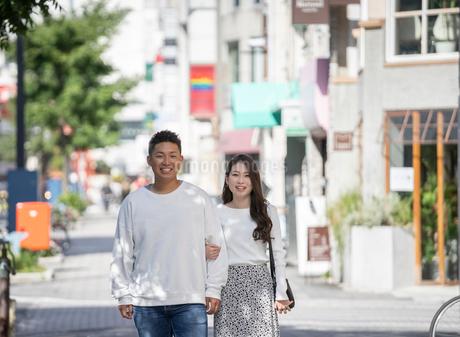 街中で仲良くデートをする若い男女の写真素材 [FYI03414275]
