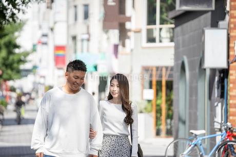 街中で仲良くデートをする若い男女の写真素材 [FYI03414276]