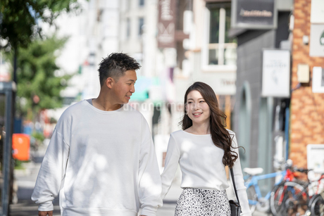 街中で仲良くデートをする若い男女の写真素材 [FYI03414283]