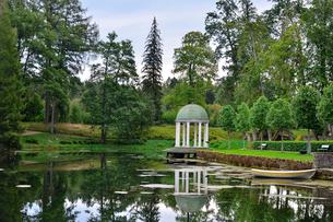 エストニア・北部にある18世紀の建物でエストニアで最も早く修復された領主の館のパルムセの館(現在は公園の情報センターや博物館として使用)の敷地内にあるロタンダ(基面が円形の建物)と木々に囲まれた池の映り込みの写真素材 [FYI03414675]
