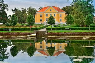エストニア・北部にある18世紀の建物でエストニアで最も早く修復された領主の館のパルムセの館(現在は公園の情報センターや博物館として使用)本館とボートと浮き輪と木々と池に映る映り込みの写真素材 [FYI03414679]