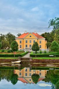 エストニア・北部にある18世紀の建物でエストニアで最も早く修復された領主の館のパルムセの館(現在は公園の情報センターや博物館として使用)本館とボートと浮き輪と池に映る映り込みの写真素材 [FYI03414680]
