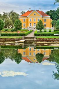 エストニア・北部にある18世紀の建物でエストニアで最も早く修復された領主の館のパルムセの館(現在は公園の情報センターや博物館として使用)本館とボートと浮き輪と池に映る映り込みの写真素材 [FYI03414681]