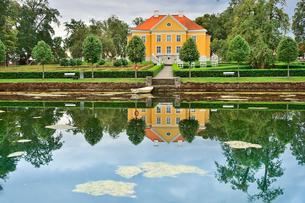 エストニア・北部にある18世紀の建物でエストニアで最も早く修復された領主の館のパルムセの館(現在は公園の情報センターや博物館として使用)本館と並ぶ木々と池に映る映り込みの写真素材 [FYI03414682]