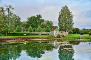 エストニア・北部にある18世紀の建物でエストニアで最も早く修復された領主の館のパルムセの館(現在は公園の情報センターや博物館として使用)敷地内に作られたコーヒーハウスと並ぶベンチと木々と池に映る映り込みの写真素材 [FYI03414683]
