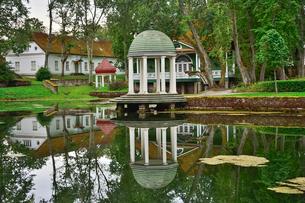 エストニア・北部にある18世紀の建物でエストニアで最も早く修復された領主の館のパルムセの館(現在は公園の情報センターや博物館として使用)敷地内に作られたロタンダ(基面が円形の建物)と休憩所と池に映る映り込みの写真素材 [FYI03414684]