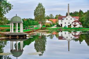 エストニア・北部にある18世紀の建物でエストニアで最も早く修復された領主の館のパルムセの館(現在は公園の情報センターや博物館として使用)敷地内に作られた蒸留所や醸造所などの建物と池に映る映り込みの写真素材 [FYI03414691]