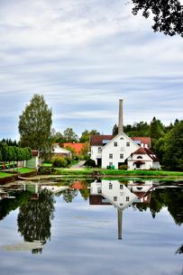 エストニア・北部にある18世紀の建物でエストニアで最も早く修復された領主の館のパルムセの館(現在は公園の情報センターや博物館として使用)敷地内に作られた蒸留所や醸造所などの建物と池に映る映り込みの写真素材 [FYI03414692]