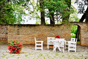 エストニア・北部にある18世紀の建物でエストニアで最も早く修復された領主の館のパルムセの館(現在は公園の情報センターや博物館として使用)の電飾が設置された木とイスとテーブルの写真素材 [FYI03414700]