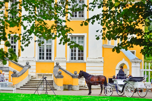エストニア・北部にある18世紀の建物でエストニアで最も早く修復された領主の館のパルムセの館(現在は公園の情報センターや博物館として使用)の本館の庭園を一周巡る観光馬車の写真素材 [FYI03414717]