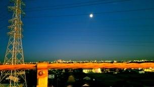 柵と鉄塔と街と月の写真素材 [FYI03414774]