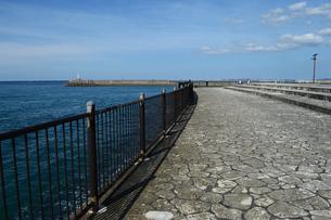 防波堤の灯台と海沿いの遊歩道の写真素材 [FYI03415120]