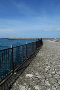 防波堤の灯台と海沿いの遊歩道の写真素材 [FYI03415125]