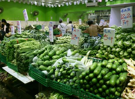 香港の下町「北角」の市場で野菜を売る店。瓜、ニガウリ、ササゲ、チンゲン菜が山積みになって、売られている。の写真素材 [FYI03415478]