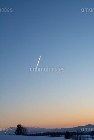 冬の夕暮れの空と飛行機雲の写真素材 [FYI03415829]