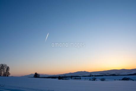 冬の夕暮れの空と飛行機雲の写真素材 [FYI03415830]