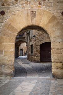 スペインの中世の田舎村の石でできたアーチと石畳の道の写真素材 [FYI03416095]