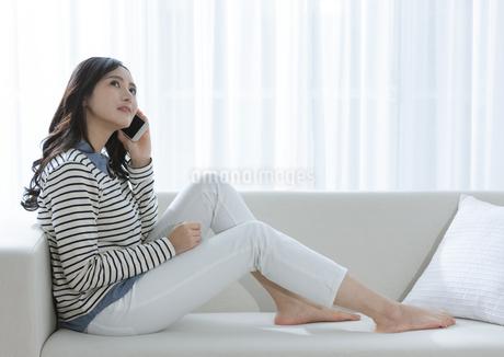 ソファーで電話する女性の写真素材 [FYI03416619]