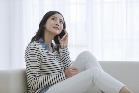 ソファーで電話する女性の写真素材 [FYI03416620]