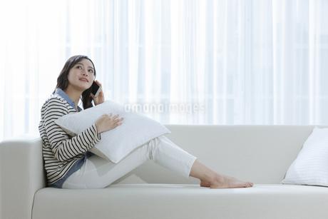 ソファーで電話する女性の写真素材 [FYI03416621]
