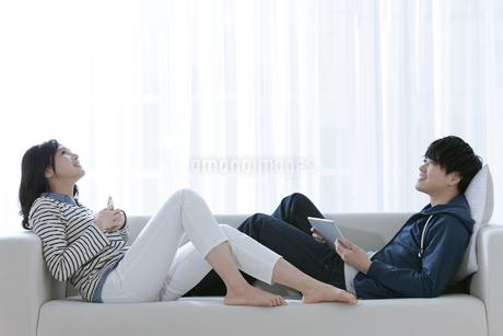ソファーでくつろぐカップルの写真素材 [FYI03416654]