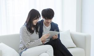 タブレットPCを見るカップルの写真素材 [FYI03416656]