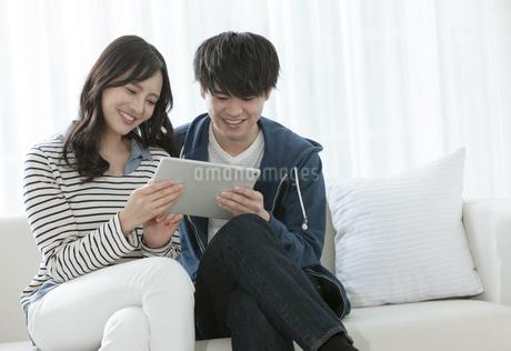 タブレットPCを見るカップルの写真素材 [FYI03416658]