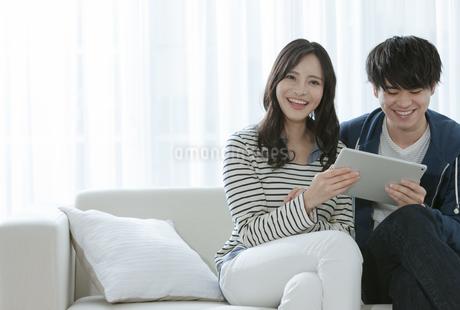 タブレットPCを見るカップルの写真素材 [FYI03416659]