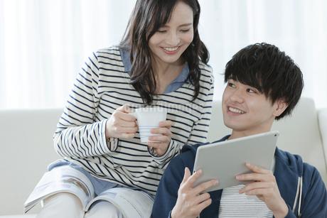タブレットPCを見るカップルの写真素材 [FYI03416662]