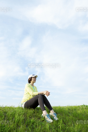 土手に座るスポーツウェア姿の女性の写真素材 [FYI03416877]