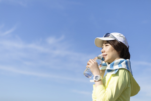 運動中に水分補給する女性の写真素材 [FYI03416892]
