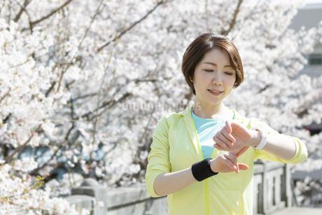 運動中に時計を見る女性の写真素材 [FYI03416909]