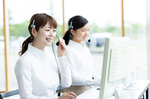電話応対をするオペレーター女性の写真素材 [FYI03417003]
